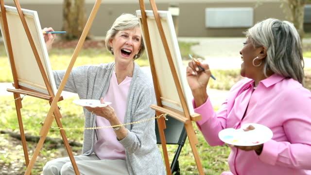 vidéos et rushes de deux femmes âgées bavarder tout en peinture sur toile - activité