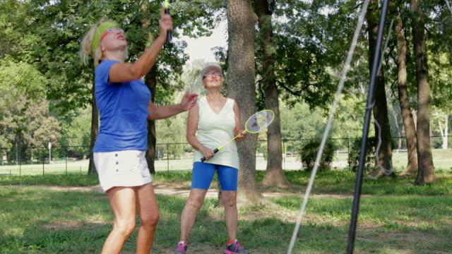 vídeos de stock, filmes e b-roll de duas mulheres sênior felizes por marcar no jogo de badminton - badmínton esporte