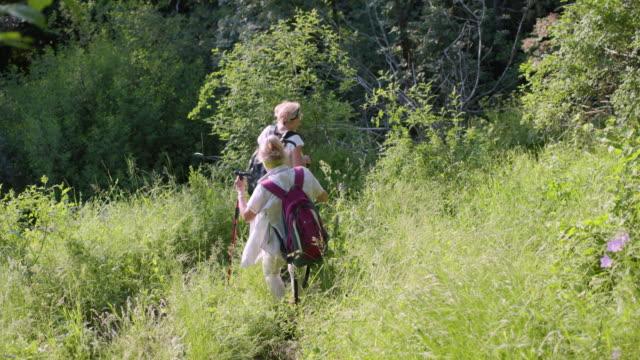Two senior women hiking down steep grass area