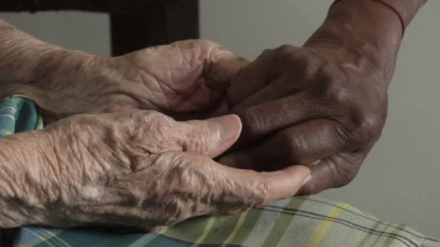 cu two senior women holding hands in nursing home / trinidad and tobago - care stock videos & royalty-free footage
