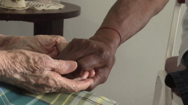 cu two senior women holding hands in nursing home / trinidad and tobago - holding hands stock videos & royalty-free footage