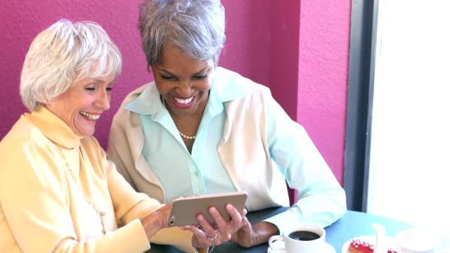 stockvideo's en b-roll-footage met twee senior vrouwen kijken naar telefoon in coffeeshop - 70 79 jaar