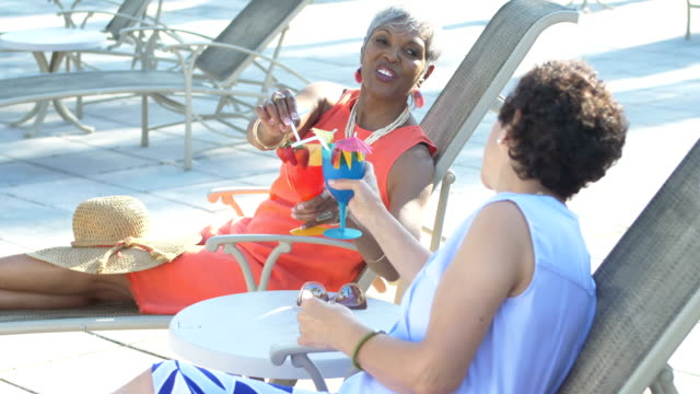 two senior women on lounge chairs, drinking, talking - lido stock videos & royalty-free footage