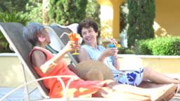Two senior women on lounge chairs, drinking, talking