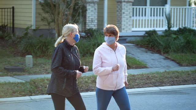 vídeos de stock e filmes b-roll de two senior women power walking, wearing face masks - andar depressa