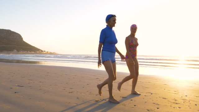 two senior women running into sea at dawn - gegenlicht stock-videos und b-roll-filmmaterial