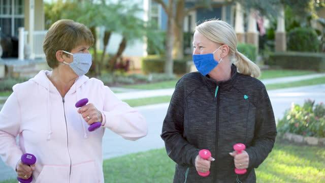 vídeos de stock e filmes b-roll de two senior women walking with hand weights, face masks - andar depressa