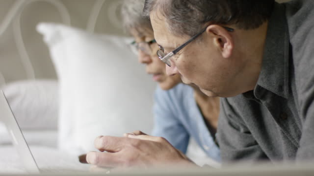 Two Senior-Age Adults Laying on a Bed while Using a Laptop Computer