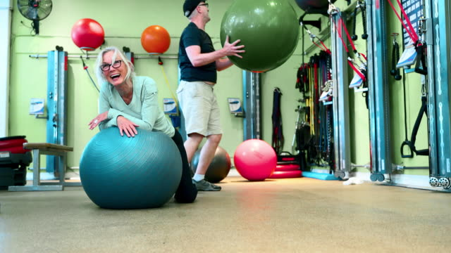 two seniors, man, and woman, doing fitness stretching and gymnastic workout with fitness balls together in the gym. they finishing the exercise and laughing. - fitness ball stock videos & royalty-free footage