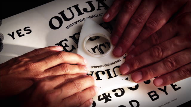 two sets of hands rest on a planchette as it travels across a ouija board. - forecasting stock videos & royalty-free footage