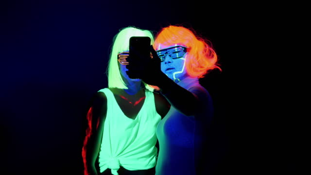 two sexy cyber glow raver women filmed in fluorescent clothing under uv black light and using smartphone women taking selfies - selfie video stock e b–roll