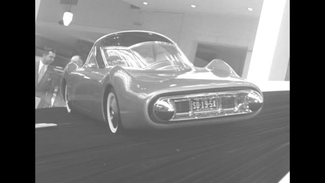 stockvideo's en b-roll-footage met two shiny new cars on a revolving tilted turntable / high angle view of exhibits at car show / futuristic concept car on turntable / tilted view of... - chrysler