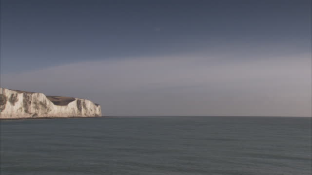 Two ships move out at sea near the white Cliffs of Dover.