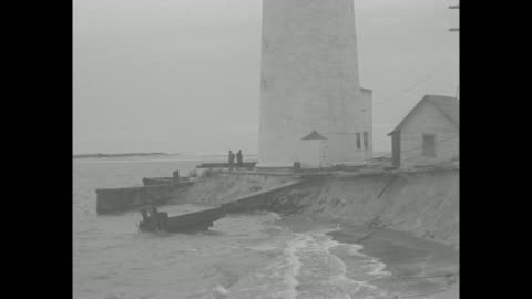 vídeos de stock, filmes e b-roll de two ships ride heavy waves / barnegat lighthouse / the base of the lighthouse with two men / a house tilted into the water, waves batter it with a... - oceano atlântico