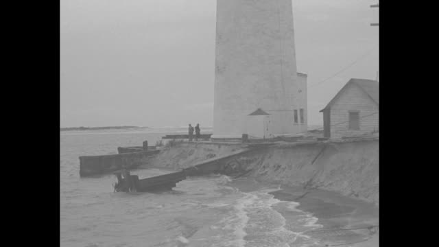 vídeos de stock, filmes e b-roll de two ships ride heavy waves / barnegat lighthouse / the base of the lighthouse with two men / a house tilted into the water waves batter it with a... - oceano atlântico