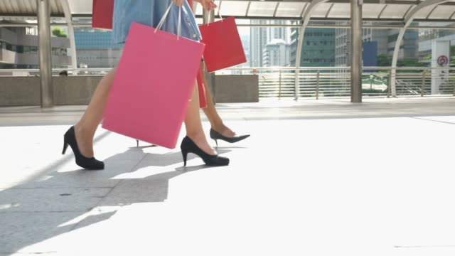 Two shopaholics woman walking with Shopping Bag