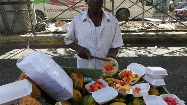 vídeos de stock, filmes e b-roll de santo domingo dominican republic november 30 2012 a two shot of a young man on a market stand cutting different kinds of fruits with a big knife... - dada de cartas