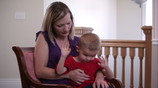 Two shot of mother holding her blind son in her lap.