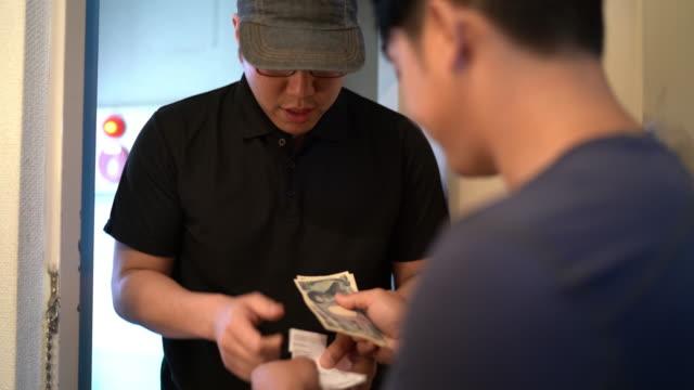 顧客の家に食べ物を届ける2ショットアジア人男性 - 小荷物点の映像素材/bロール