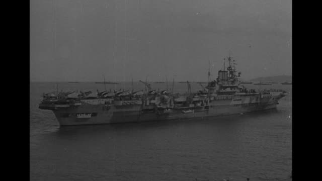 two shots from moving boat of shoreline near hong kong / view from boat of hong kong harbor / british aircraft carrier hms indomitable / plane taking... - 1940~1949年点の映像素材/bロール