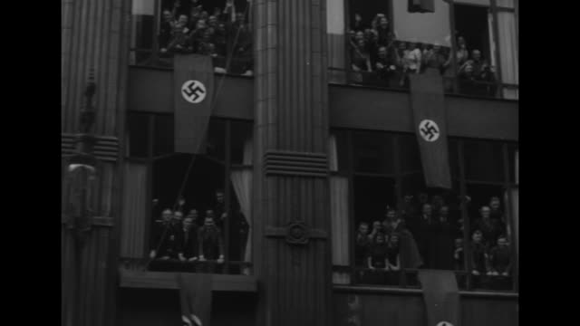 stockvideo's en b-roll-footage met two shots from moving camera of german soldiers standing at attention in formation / shot from moving vehicle of cheering crowd on sidewalk / three... - nazism