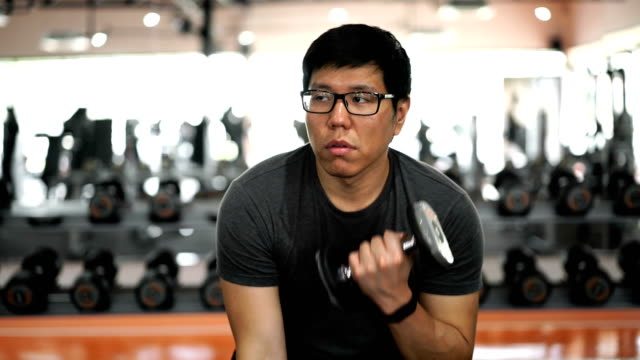 vídeos de stock, filmes e b-roll de dois tiros homem entediado de fazer haltere de rotinas de treino no ginásio - musculação