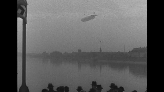 two shots of airship flying over bridge over rhine river in cologne / airship flying over rhine river and buildings of city, people watching and nazi... - newsreel stock videos & royalty-free footage