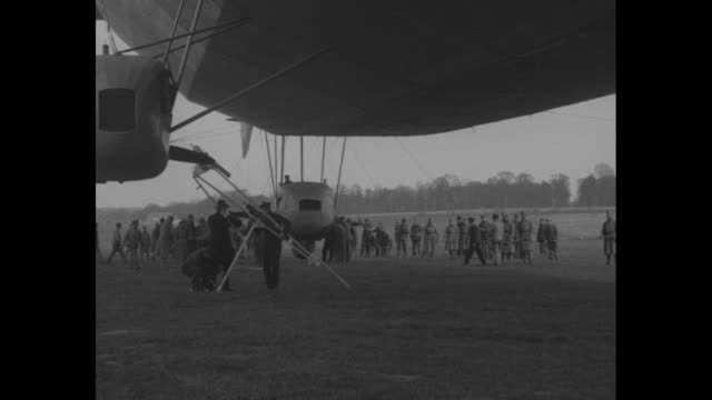 two shots of airship mediterranee being moved from hangar / men on ground pulling airship into position with ropes / men on ground under airship as... - campo d'aviazione video stock e b–roll