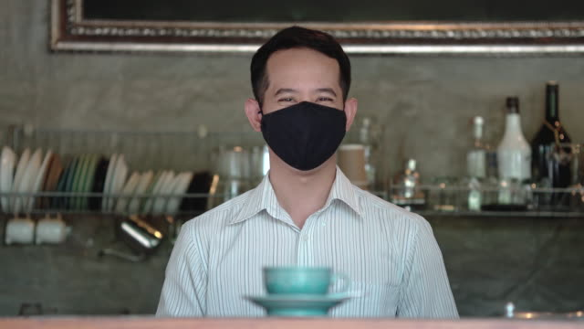 two shots of asian male barista serving hot beverage and smile behind a mask - obscured face stock videos & royalty-free footage