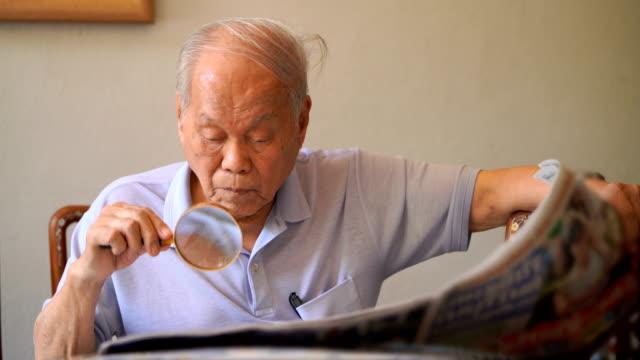 vidéos et rushes de deux coups d'asiatique vieil homme lisant un journal - brightly lit