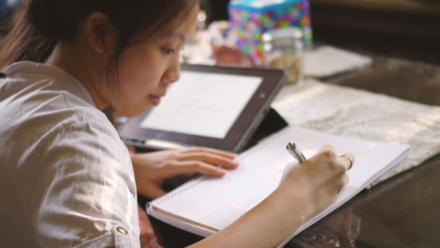 two shots of asian school girl concentrates on her e-learning - note pad stock videos & royalty-free footage