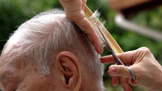 two shots of asian senior having outdoor haircut - human head stock videos & royalty-free footage