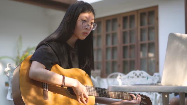 vidéos et rushes de deux plans d'adolescente asiatique apprenant des cordes de guitare de l'ordinateur portatif - guitare