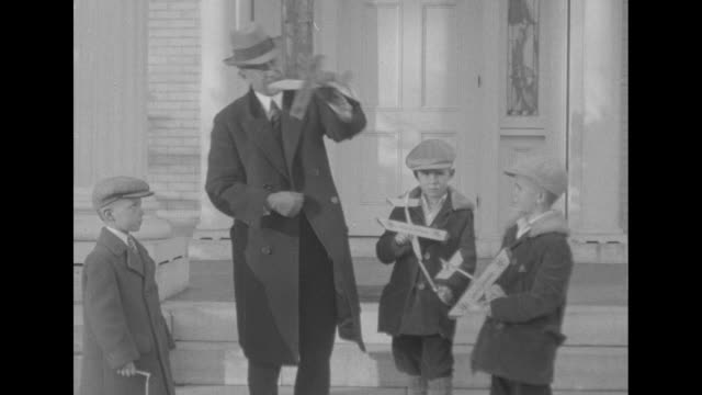two shots of aviation pioneer orville wright standing with toy glider he is holding demonstrating glider to three boys standing in front of him... - 1900 1909 video stock e b–roll