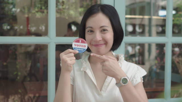"""two shots of black haired woman pointing at her """"i voted"""" sticker - us president stock videos & royalty-free footage"""
