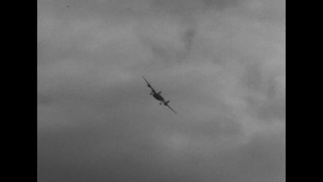 two shots of bomber flying low overhead / pilot floating down in parachute / pilot landing on ground / note exact day not known - parachuting stock videos & royalty-free footage
