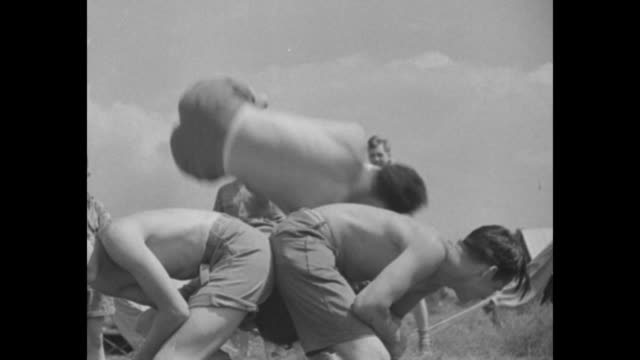 two shots of boys scouts playing version of leap frog during jamboree / person putting food in container / person shoving food container down short... - hoppa bock bildbanksvideor och videomaterial från bakom kulisserna