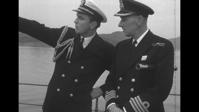 Two shots of British captain of HMS Prince of Wales talking to US Navy officer / VS US and British Navy officers talking to one another standing...