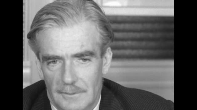 Two shots of British Foreign Secretary Anthony Eden sitting at desk speaking to reporters about his justcompleted visit with members of US...