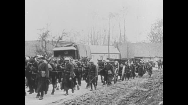 two shots of british soldiers marching along road guiding horses pulling wagons / french soldiers on horses guarding german pows as they march along... - french army stock videos & royalty-free footage