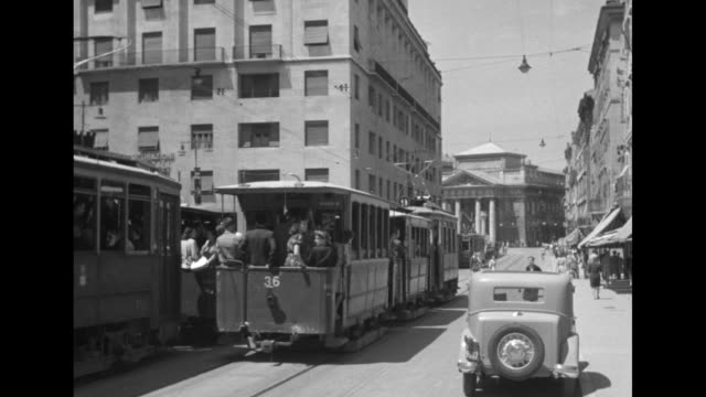 two shots of cars driving down street and people walking on sidewalks and crossing street / two trams going in opposite directions down street pass... - 1946 stock-videos und b-roll-filmmaterial
