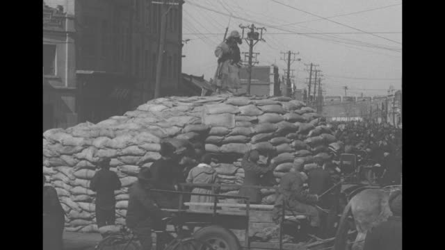 two shots of chinese soldiers walking along street / chinese soldier with rifle standing atop guard station made of sandbags people looking up at him... - 満州地方点の映像素材/bロール