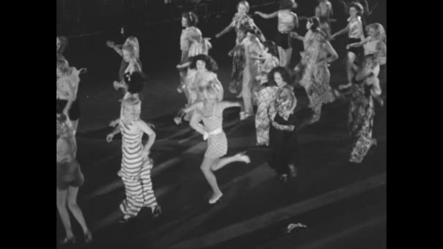 Two shots of chorus girls practicing dance routine / two close views of girls practicing dance routine / girls walking around stage / close view of...