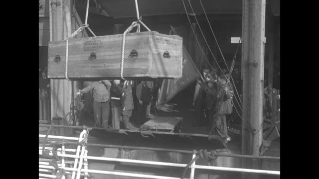 two shots of coffin being lifted by crane from ship and swung onto cart on pier man with american flag and another man with a different flag stand... - 棺点の映像素材/bロール