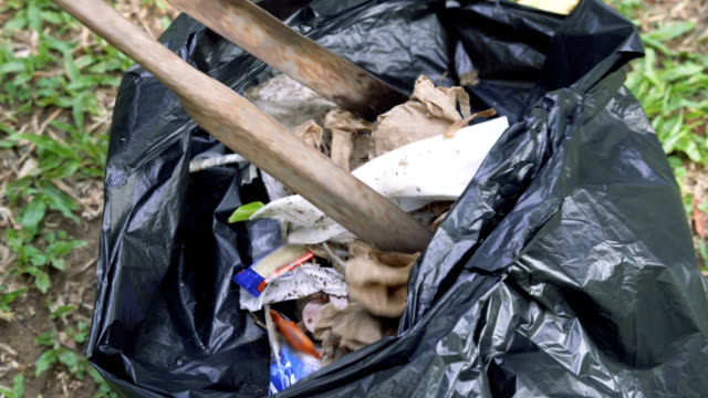 two shots of collecting garbage into a bag - washing up glove stock videos & royalty-free footage