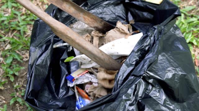 stockvideo's en b-roll-footage met twee shots van het verzamelen van vuilnis in een zak - afwashandschoen