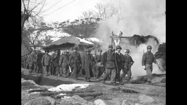 Two shots of column of ROK soldiers marching along road past smoke rising from demolished hut / Note exact month/day not known