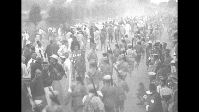 two shots of column of soldiers of national revolutionary army marching down street as they evacuate city crowd on either side / chiang kaishek... - chiang kai shek stock-videos und b-roll-filmmaterial
