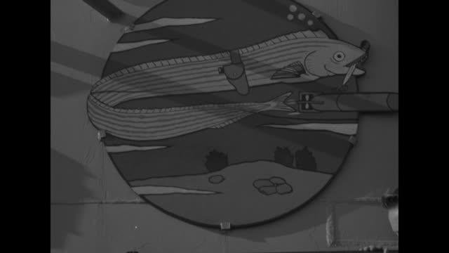 two shots of crew of submarine tirante standing on top of conning tower / members of crew looking at large scorecard of japanese ships they have sunk... - luftvärn bildbanksvideor och videomaterial från bakom kulisserna