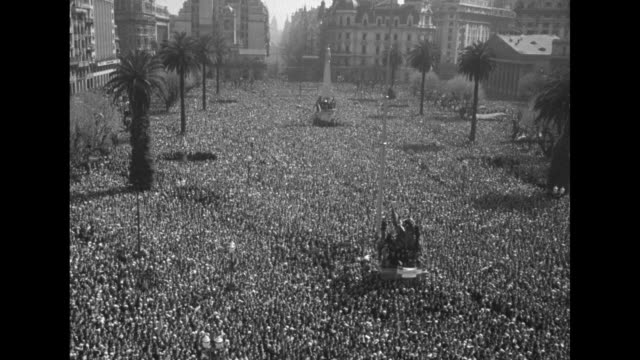 vídeos de stock e filmes b-roll de two shots of eduardo lonardi provisional president of argentina taking oath of office surrounded by heads of new government / ws huge crowd in plaza... - 1955